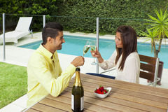 Young couple toasting with champagne. In a modern backyard with swimming pool Royalty Free Stock Photos