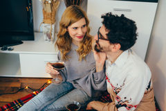 Young couple toasting with cocktail glasses at home. In living room, girl touching guy's beard royalty free stock image