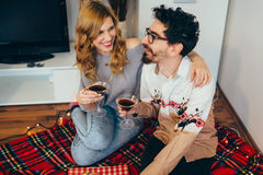 Young couple toasting with cocktail glasses at home. In living room, laughing stock photos