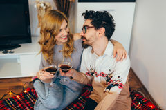 Young couple toasting with cocktail glasses at home. In living room, smiling royalty free stock photo