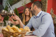 Young couple toasting with wine and communicating in a restauran Royalty Free Stock Images