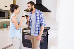 Young couple toasting wine glass in kitchen Stock Images