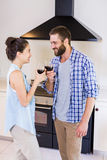 Young couple toasting wine glass in kitchen Royalty Free Stock Photos