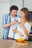 Young couple toasting wine in kitchen. Young couple toasting wine while standing in kitchen at home royalty free stock photos