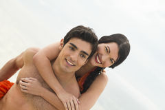 Young couple together. A happy women wraps her arms around a man Stock Image
