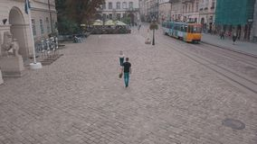 Young couple together in the center of the street. Man with a bouquet of flowers. Shooting from the air. Aerial shot stock video footage