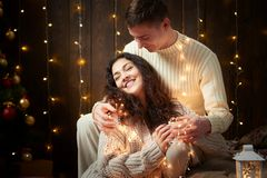 Young couple together in christmas lights and decoration, dressed in white, fir tree on dark wooden background, romantic evening,. Winter holiday concept Stock Images