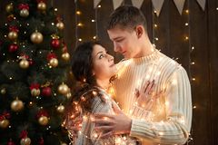 Young couple together in christmas lights and decoration, dressed in white, fir tree on dark wooden background, romantic evening,. Winter holiday concept Stock Photos
