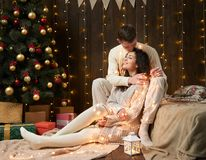 Young couple together in christmas lights and decoration, dressed in white, fir tree on dark wooden background, romantic evening,. Winter holiday concept Royalty Free Stock Photos
