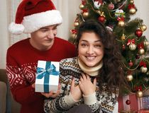 Young couple together with christmas tree and gifts in home interior - love and holiday concept, xmas eve Royalty Free Stock Photo