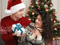Young couple together with christmas tree and gifts in home interior - love and holiday concept, xmas eve Stock Photos