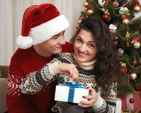 Young couple together with christmas tree and gifts in home interior - love and holiday concept, xmas eve Stock Photography