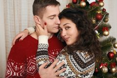 Young couple together with christmas tree in home interior - love and holiday concept, xmas eve Stock Photo