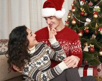 Young couple together with christmas tree in home interior - love and holiday concept, xmas eve Stock Photos