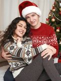 Young couple together with christmas tree in home interior - love and holiday concept, xmas eve Royalty Free Stock Photo