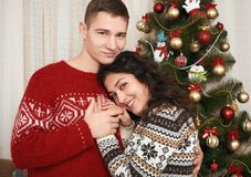 Young couple together with christmas tree in home interior - love and holiday concept, xmas eve Royalty Free Stock Image