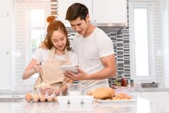 Young couple together cooking, Woman first crack an egg and put in a bowl. Man holding tablet looking menu for dinner bakery bread cake with milk in kitchen Royalty Free Stock Images