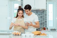Young couple together cooking, Woman first crack an egg. And put in a bowl, Man holding tablet looking menu for dinner bakery bread cake with milk in kitchen Stock Photo