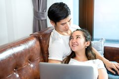 Young couple together man and woman. Young couple together men and women looking laptop computer happy and smile relaxing on sofa in living room at home in Royalty Free Stock Photo