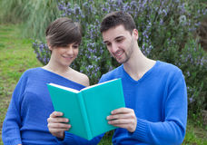 Young couple together reading a book together in the park Royalty Free Stock Photos