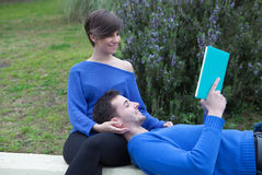 Young couple together reading a book together in the park Royalty Free Stock Images