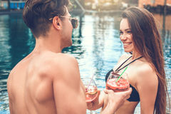 Young couple together relax in the swimming pool. Young men and women together in the swimming pool drink Stock Photos