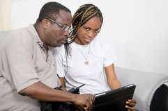 Young couple together using a laptop. This gentleman is trying to show this women how to use some applications on a computer Stock Photography
