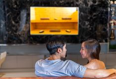 Young couple together watching tv with sauna spa in resort. Program and sitting sofa in living room at home happy romantic resting relax for honeymoon in Stock Images