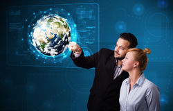 Young couple touching high-tech 3d earth panel Stock Images