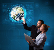 Young couple touching high-tech 3d earth panel Royalty Free Stock Image