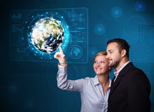Young couple touching high-tech 3d earth panel Stock Image