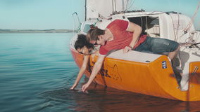 Young couple touching seawater stock video footage
