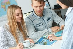 Young couple in a tour agency communication with a travel agent travelling concept booklet. Young men and women smiling in a tour agency with a travel agent Royalty Free Stock Images