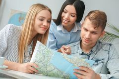 Young couple in a tour agency communication with a travel agent travelling concept choosing destination on a map. Young men and women in a tour agency with a Royalty Free Stock Images