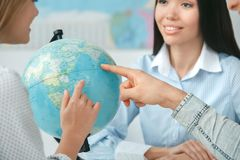 Young couple in a tour agency communication with a travel agent travelling concept globe choosing destination close-up. Young men and women in a tour agency with Stock Photos