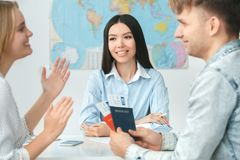 Young couple in a tour agency communication with a travel agent travelling concept holding documents excited. Young men and women in a tour agency with a travel Stock Image
