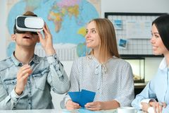 Young couple in a tour agency communication with a travel agent travelling concept virtual reality headset excited. Young men wearing virtual reality headset Stock Photos