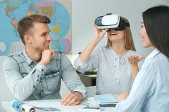 Young couple in a tour agency communication with a travel agent travelling concept virtual reality headset. Young men and women wearing virtual reality headset Royalty Free Stock Image