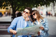 Young couple tourist with map pointing to a landmark backpackers in the city royalty free stock images