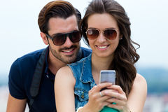 Young couple of tourist in town using mobile phone. Stock Photo