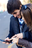Young couple of tourist in town using mobile phone. Stock Image