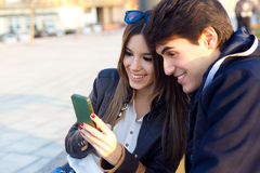 Young couple of tourist in town using mobile phone. Royalty Free Stock Images