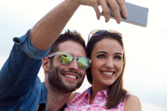 Young couple of tourist in town using mobile phone. Stock Photos