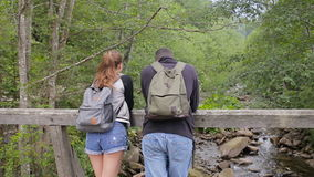 Young couple of tourists with backpacks on a bridge over a mountain river.  stock footage