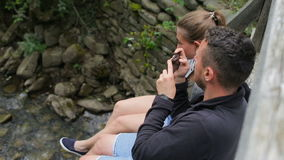 Young couple of tourists with backpacks on a bridge over a mountain river. Make a photo of the feet on the background of. The river stock video footage