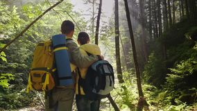 Young couple of tourists with backpacks in the forest. Stand nearby, admire the rays of the rising sun. Back view. 4K video stock video