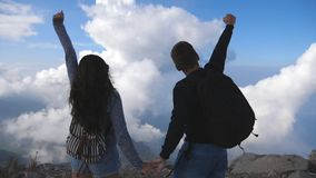 Young couple of tourists with backpacks reaching up top of mountain and raised hands. Man and woman standing on edge of stock video