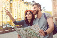 Young couple tourists city walk together vacation. Young couple women and men tourists city walk together vacation holding map Royalty Free Stock Images
