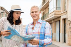 Young couple of tourists consulting a map. Trendy attractive young couple of tourists consulting a map as they search for their destination while out sightseeing Stock Photo