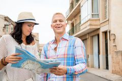 Young couple of tourists consulting a map. Trendy attractive young couple of tourists consulting a map as they search for their destination while out sightseeing Stock Images